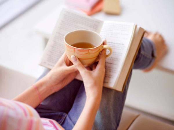 женщина пьет кофе чай и читает книгу