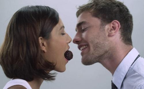 девушка угощает парня шоколадом изо рта