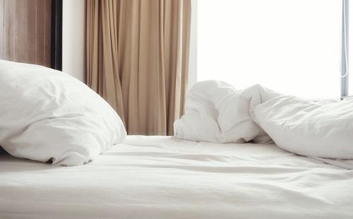чистая свежая белая постель на двухспальной кровати