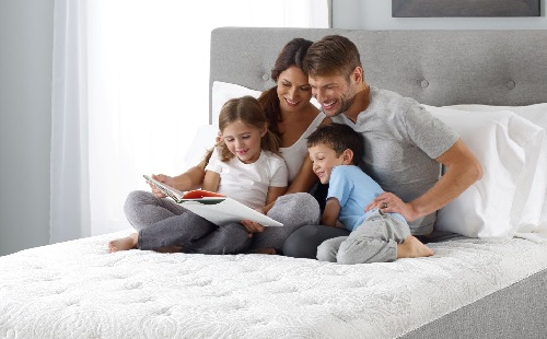 родители и дети сидят на белой чистой кровати и читают книгу