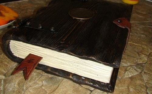 на столе лежит красивая старинная книга с закладкой