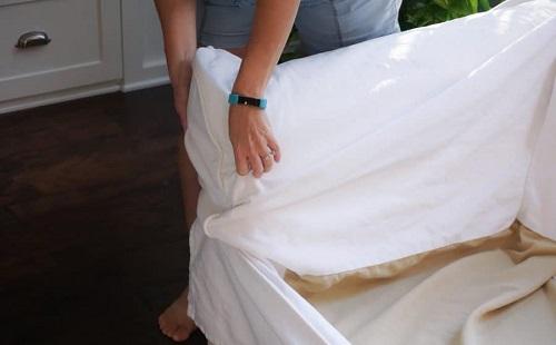 женщина снимает чехол с дивана перед стиркой
