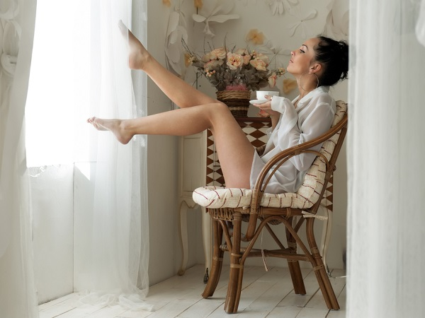 девушка пьет чай сидя на стуле и смотрит в окно
