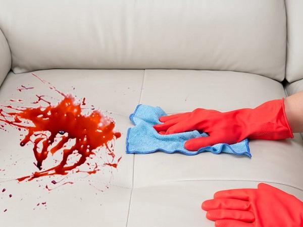 на кожаном диване кресле разлит чай кофе девушка чистит его в резиновых перчатках