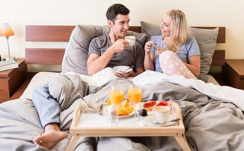 девушка и парень завтракают в белой постели