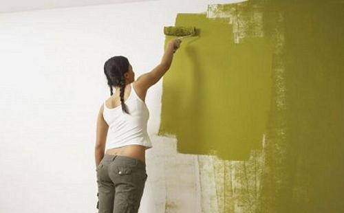 девушка красит стену в зеленый цвет