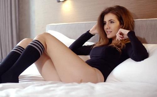 девушка в черной одежде лежит на белой постели