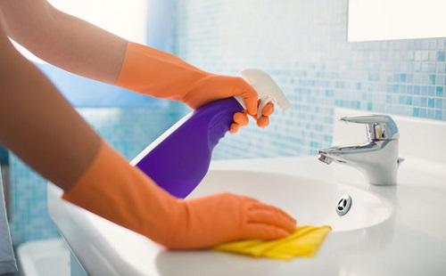Девушка чистит умывальник в перчатках
