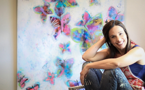 девушка сидит на полу сзади стена разрисованная бабочками и цветами