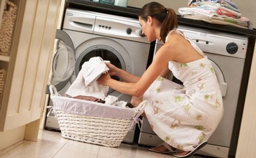 девушка в белом платье вынимает из стиральной машинки чистую белую постель