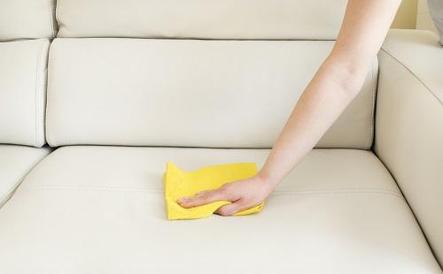 девушка чистит желтой тряпкой белый кожаный диван
