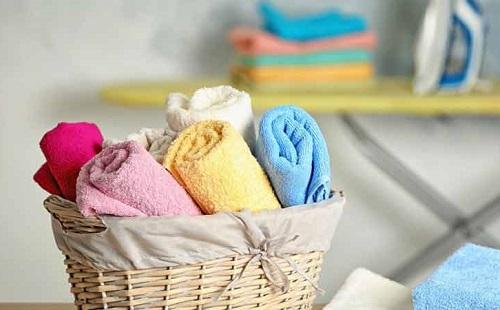 в корзинке лежат свернутые в рулоны чистые разноцветные полотенца