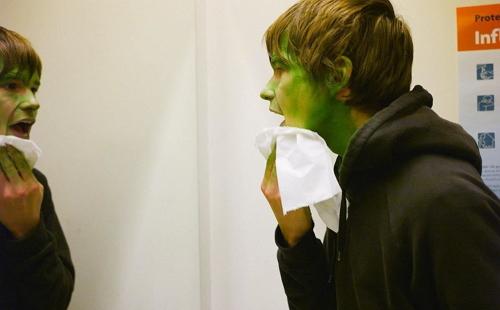 парень отчищает зеленую гуашь с лица перед зеркалом