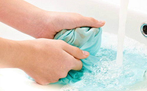 женщина стирает белье в ванной на белье бежит струя чистой воды