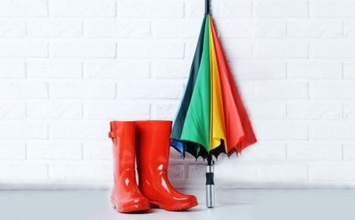 у стены стоят красные резиновые сапоги и зонтик-тросточка