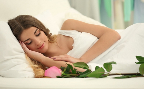девушка лежит в белой чистой постели у нее роза на длинном стебле