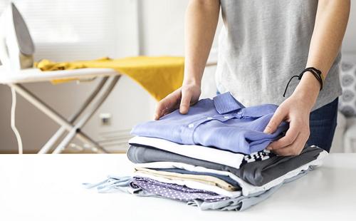 женщина складывает в стопку чистое выглаженное цветное белье