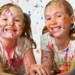 две девочки рисуют гуашью и выпачкали одежду лицо волосы ковер