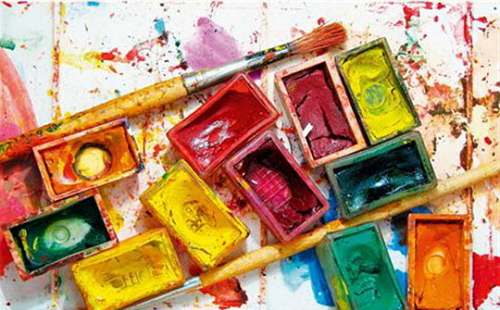 акварельные краски и кисточка лежат на столе в коробке