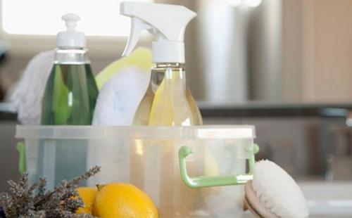 в пластиковом ящике стоят средства пятновыводители и рядом лежит лимон