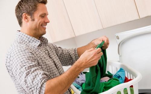 мужчина стирает вещи в тазике под проточной струей воды