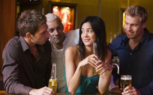 трое мужчин ухаживают за девушкой в баре