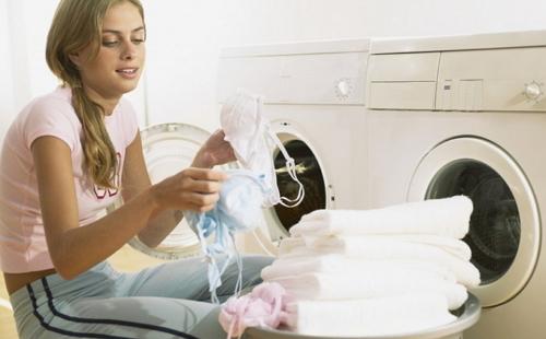 девушка силит на полу и рассматривает белье из стиральной машинки