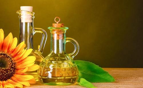 на столе стоит бутылка с подсолнечеым маслом и лежит подсолнух