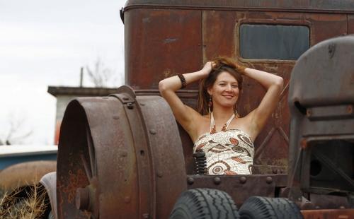 девкша сидит среди ржавых машин подняв руки вверх