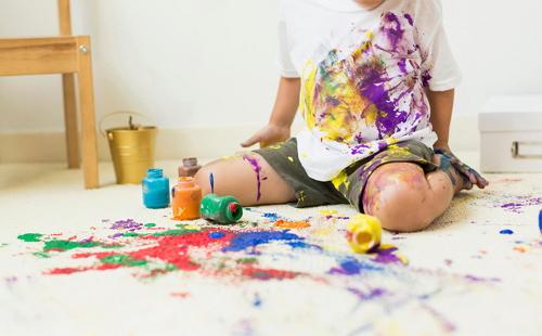 мальчик испачкал красками одежду себя и ковер и сидит