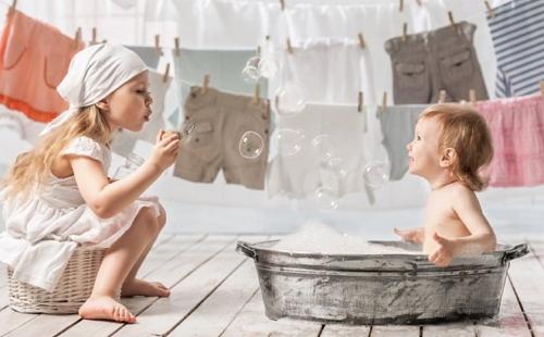 маленький мальчик купается в тазу а девочка пускает мыльные пузыри рядом висит сушится белье