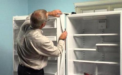 Мастер по ремонту холодильника меняет уплотнительную резинку