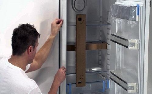 мастер по ремонту холодильников выставляет холодильник с помощью строительного уровня