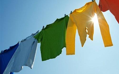 разноцветная одежда сушится на улице на веревке