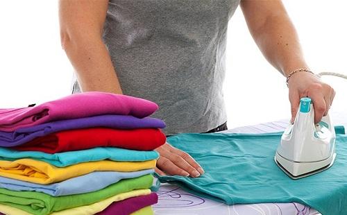женщина гладит разноцветное белье на гладильной доске