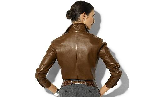 девушка в коричневой кожаной куртке стоит спиной к зрителю