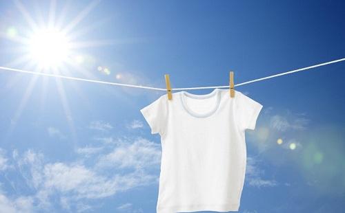 белоснежная футболка сушится на улице на веревке