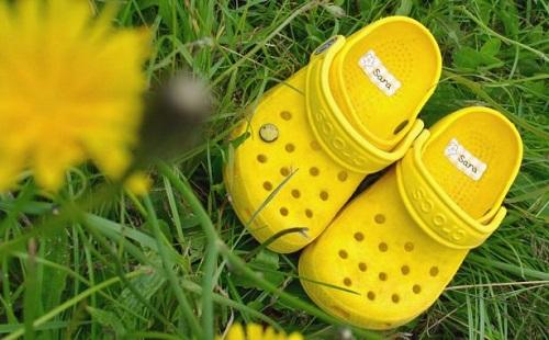 желтые босоножки стоят на зеленой траве рядом куст цветущих желтых одуванчиков