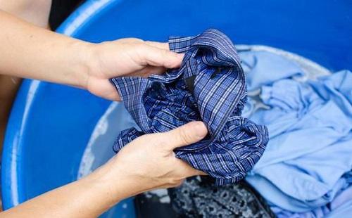 женщина стирает разноцветные вещи в синем тазу руками