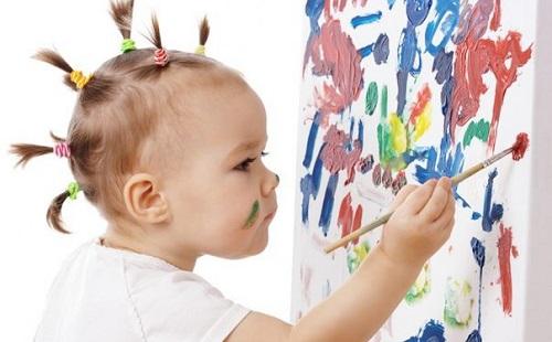 маленькая девочка разрисовывает масляными красками гуашью стенку