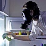 девушка в противогазе нюхает холодильник