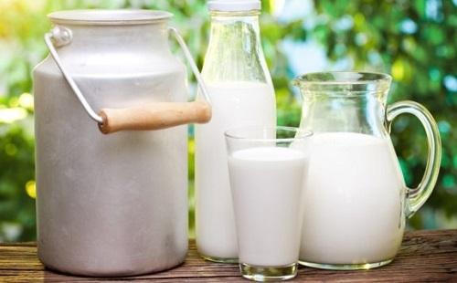 молоко в бидоне бутылке стакане банке стоит на столе