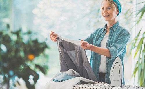 женщина улыбается и гладит чистые вещи на гладильной доске