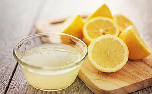 на столе лежат разрезанные пополам лимоны и стоит в прозрачной миске свежий лимонный сок