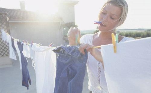красивая девушка развешивает на улице чистое белье на просушку и держит в зубах прищепку