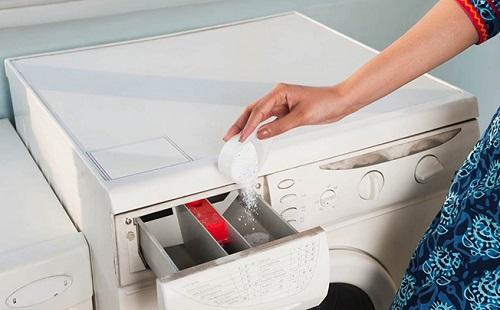 женщина засыпает в отделение для порошка в стиральной машинке стиральный порошок мерной ложкой