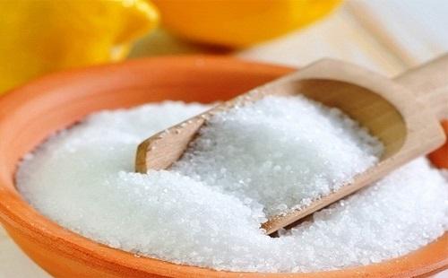 лимонная кислота в керамической миске рядом лежит два лимона