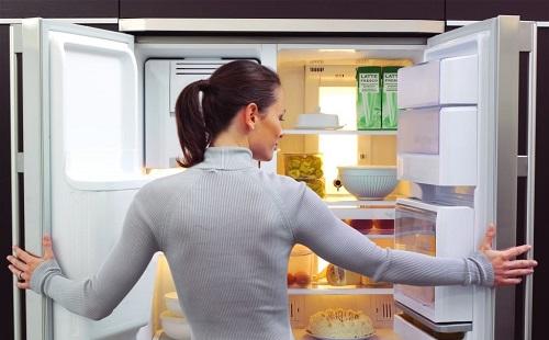 Девушка открыла чистый холодильник и смотрит