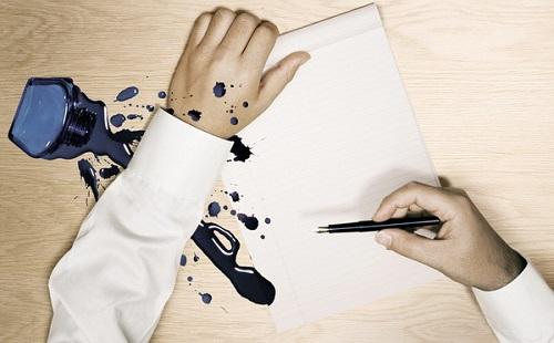 чернила разлиты на столе и на рукав белой рубашки