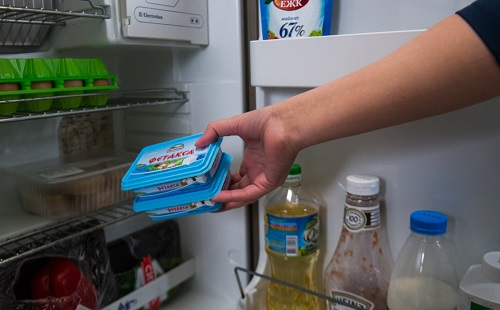 девушка ставит продукты в чистый холодильник